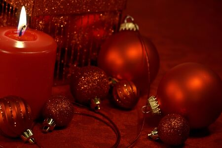 candes: Christmas ornaments and lighted candle in red Stock Photo