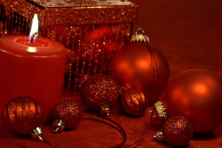 candes: Red Christmas ornaments, ribbon, candle and present on table