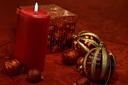 candes: Festive Christmas decorations on red tablecloth with ornaments, ribbon and lighted candle