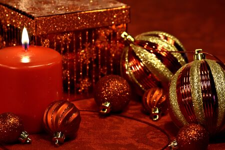 Red and gold Christmas decorations with ornaments, ribbon, present and lighted candle