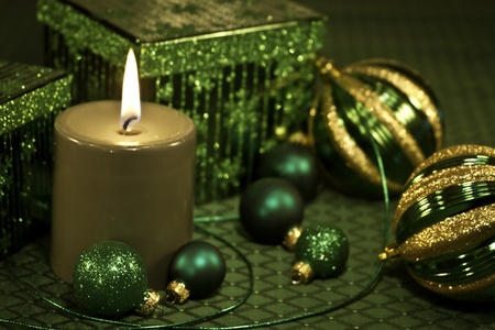 candes: Green Christmas decorations with ornaments, ribbon, present and lighted candle