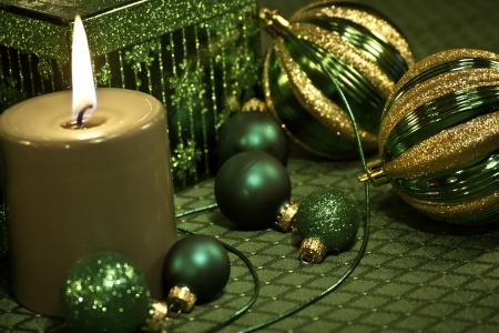 candes: Green holiday ornaments, ribbon, present and candle on green tablecloth