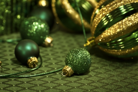 candes: Closeup of green and gold ornaments on holiday tablecloth