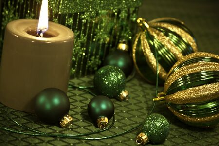 candes: Green lighted candle on table with Christmas ornaments and ribbon Stock Photo