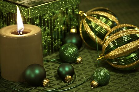 candes: Green and gold Christmas ornaments, with ribbon on festive holiday table