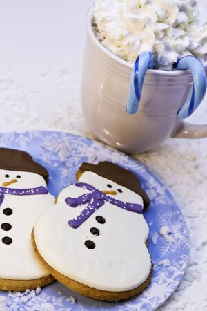 Snowman cookies on blue plate with hot chocolate photo