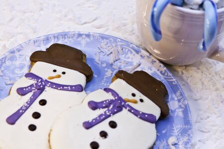 Snowman decorated cookies on blue plate with blue candy canes photo