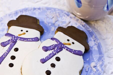 Snowman cookies with blue scarves on blue plate photo