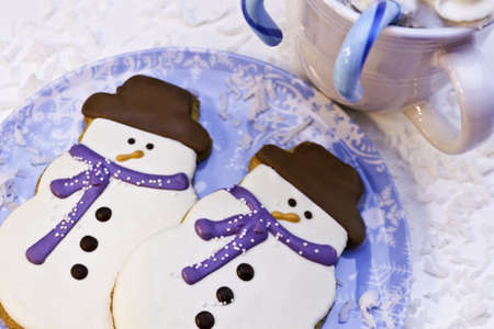Snowman cookies on blue snowflake plate with blue candy canes photo