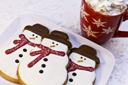 Christmas cookies in snowman shape and red mug of hot chocolate photo