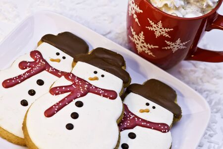 Snowman cookies on white plate with hot chocolate photo
