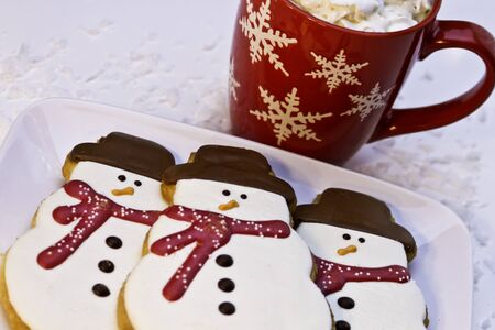 Hot chocolate in red mug with whipped cream and 3 snowman cookies photo