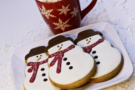 3 Christmas snowman cookies on white plate with mug of hot chocolate