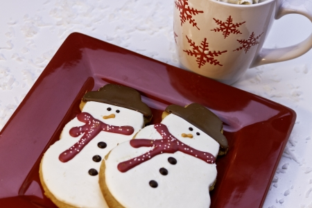 Snowman cookies with red scarves and cup of hot chocolate photo
