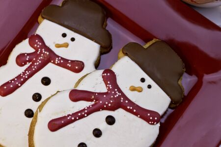 2 decorates snowman cookies on red plate photo