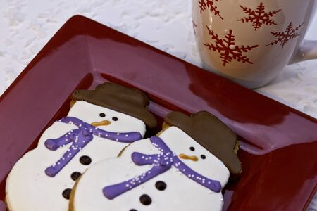 Snowman cookies for Santa on red plate with hot chocolate photo