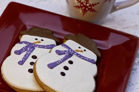 Festive decorated snowman cookies with mug of hot chocolate photo