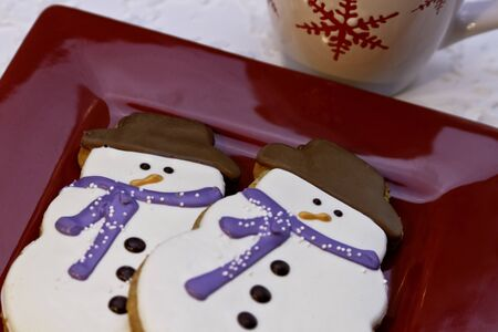 Chrismas snowman cookies on red plate with hot chocolate photo