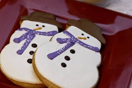 Decorated snowmen cookies with blue scarf on red plate photo