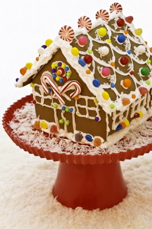Christmas gingerbread house on red cake stand with candy snow