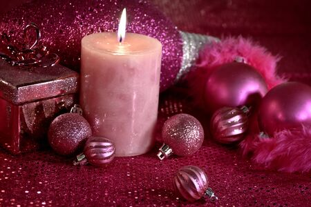 Hot pink Christmas decorations with feather garland, ornaments and lighted candle
