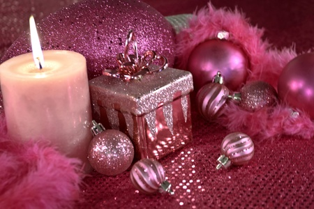 candes: Festive pink Christmas decorations on pink table cloth with lighted candle