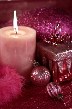 candes: Holiday decorations in pink with ornaments, feather garland and lighted candle