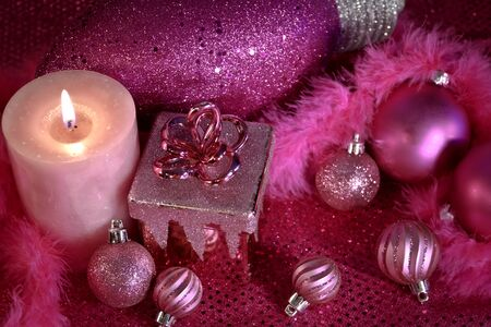 candes: Pink Christmas decorations with ornaments, present and lighted candle