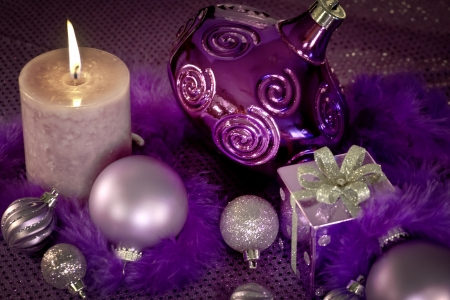 candes: Purple Christmas ornaments, present, feather garland and lighted candle