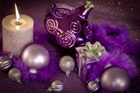 candes: Purple Christmas decorations with ornaments, present and lighted candle