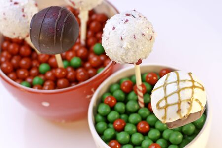 Cake pops in holiday bowls with red and green candies
