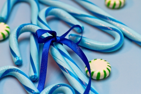 Blue candy canes tied with blue ribbon on blue background and green mints