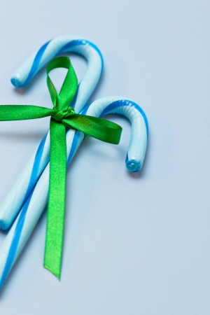 2 blue candy canes tied with green ribbon on blue background