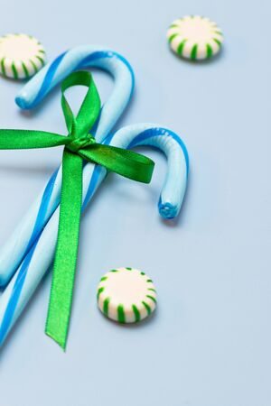 2 blue candy canes tied with green ribbon on blue background with green mints Stock fotó