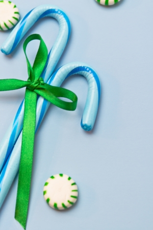 2 blue candy canes tied with green holiday ribbon on blue background and green mints