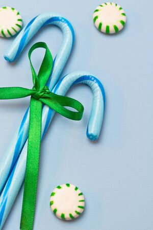 Blue candy canes tied with green holiday ribbon on blue background and green mints Stock fotó