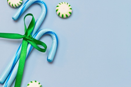 Blue holiday candy canes tied with green ribbon and green striped mints