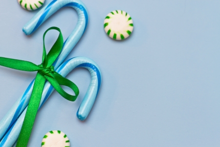 2 Blue candy canes tied with green ribbon and green striped mints on blue background