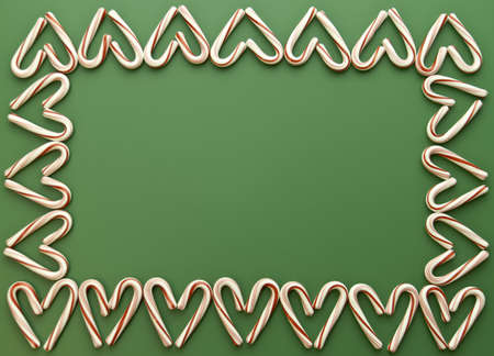 Candy cane hearts border on green background photo
