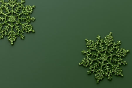 fondo verde oscuro: Copos de nieve verde del brillo en fondo verde oscuro