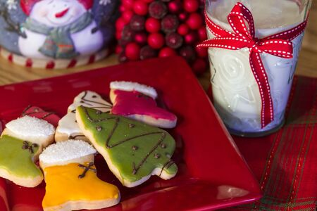 Red plate of decorated Christmas cookies with a glass of milk on Christmas table photo