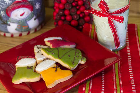 Red plate with decotated Christmas cookies and milk for Santa on a holiday table