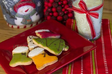 decotated: Holiday decotated table with red plate of decorated Christmas cookies and milk
