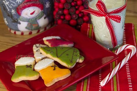 Christmas table with red plate filled with decorated Christmas cookies, candy cane and glass of milk photo
