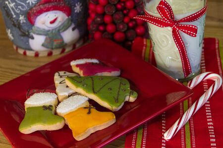 Holiday table with red plate of decorated Christmas cookies and milk, with candy cane photo