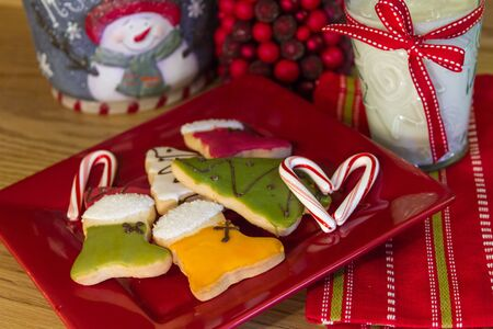 decotated: Red plate with decotated Christmas cookies and milk for Santa with a candy cane heart