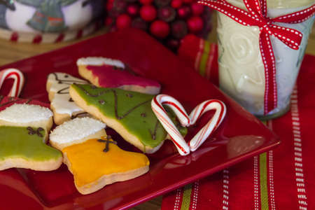 Christmas cookies and milk for Santa on a red plate with a candy cane heart photo