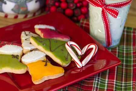 Decorated Christmas cookies and milk for Santa on red plate, with candy cane heart photo