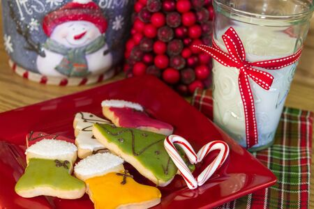 Glass of milk with red ribbon and decorated Christmas cookies on red plate photo