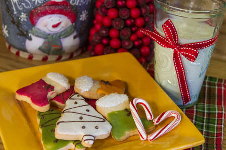 Yellow plate full of decorated Christmas cookies with candy cane heart and a glass of milk photo